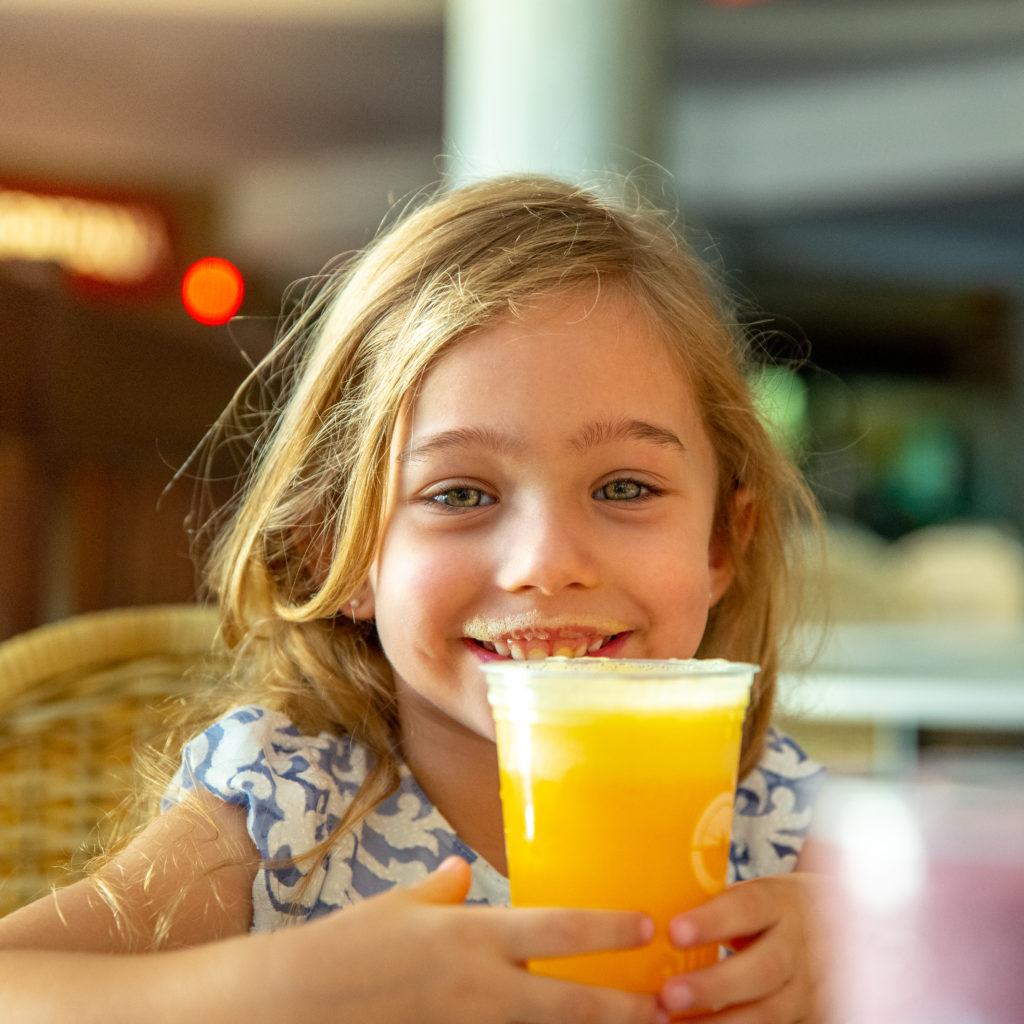 Menina loira tomando suco