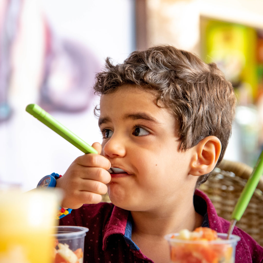 Menino comendo salada de frutas