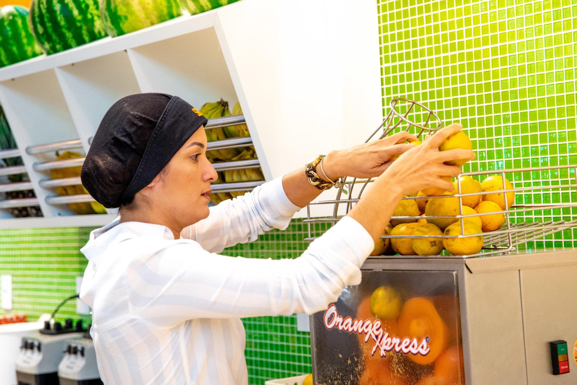 Karla repondo a máquina de laranja em sua franquia de baixo custo