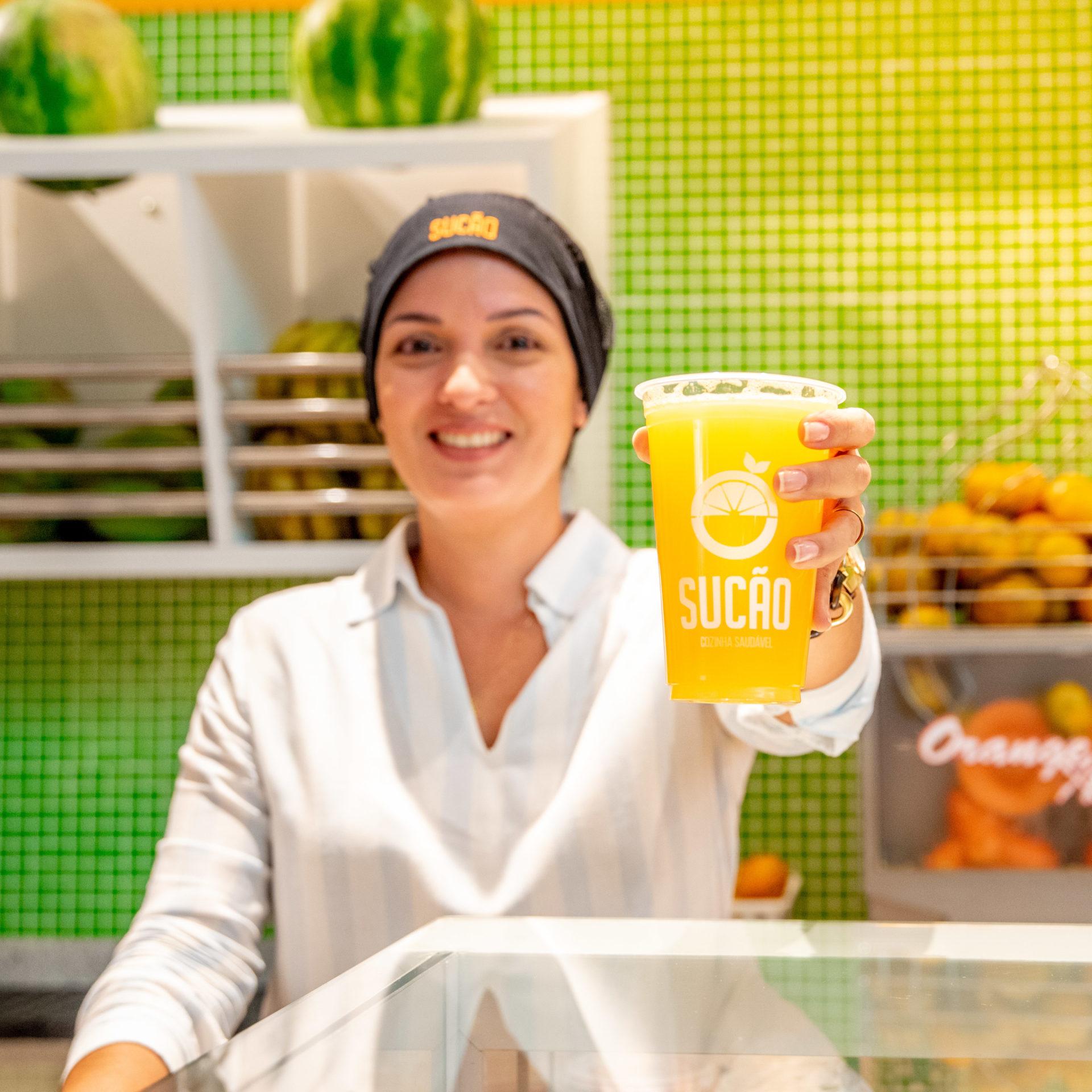 mulher de branco segurando suco de laranja em restaurante de shopping