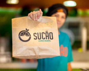 mulher segurando embalagem entrega sucão