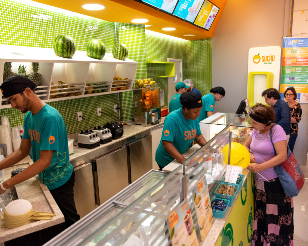 Loja de comida saudável com três atendentes dentro vestido camisetas verdes
