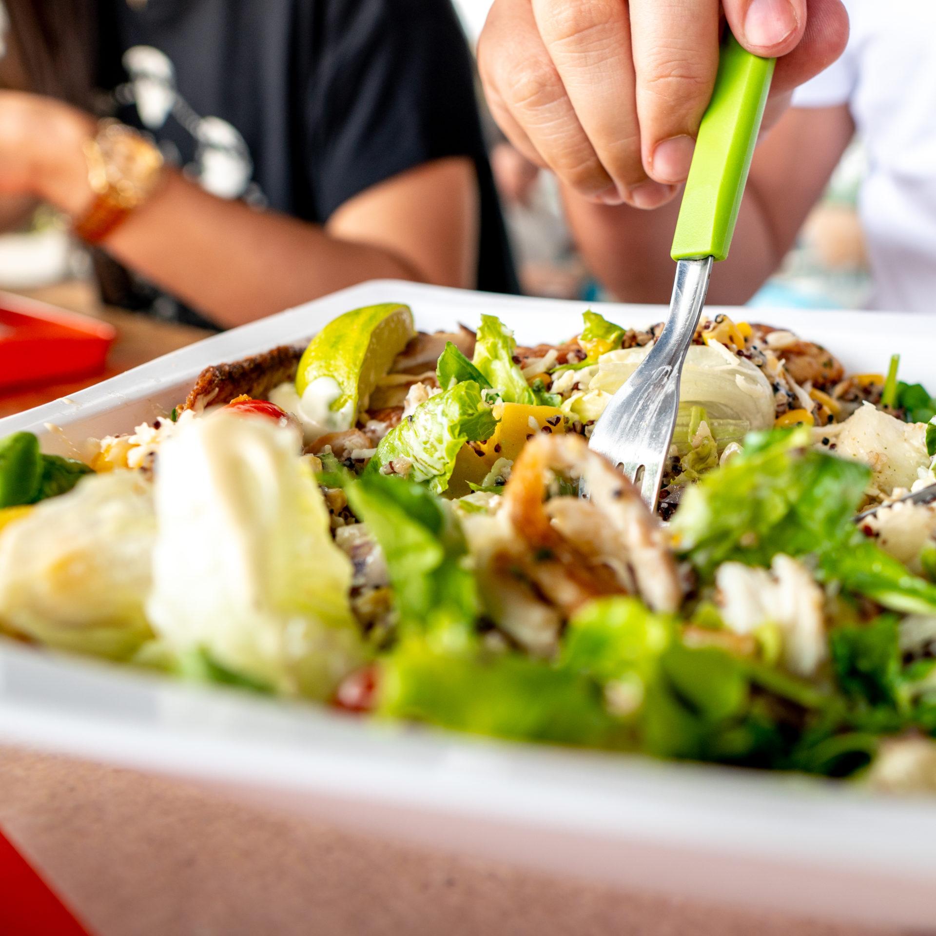 Pessoa-utilizando-garfo-verde-para-pegar-uma-salada-em-um-bowl-branco