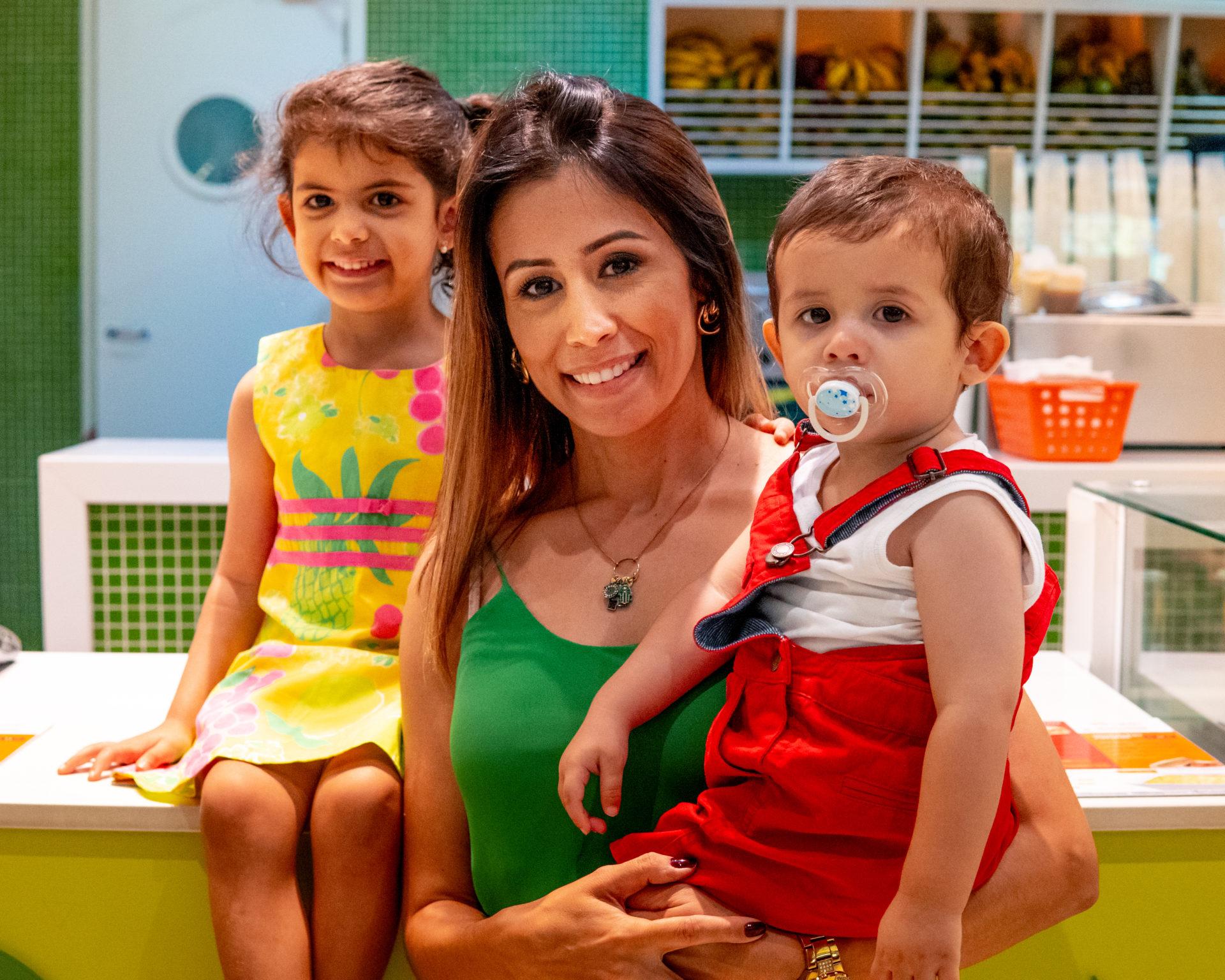 Mulher com duas crianças em frente a uma loja de sucos